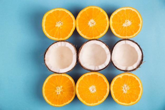 Arance mature succose e metà di cocco bianco foderate con un quadrato su un blu brillante