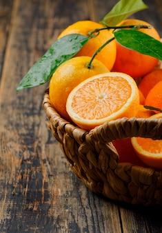 Arance succose con le foglie in un canestro di vimini sulla vecchia tavola di legno