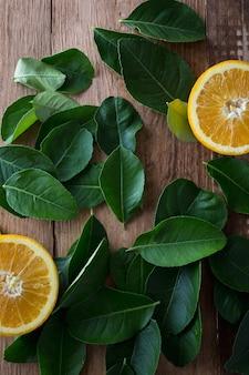 Arancia con foglie verdi su fondo in legno