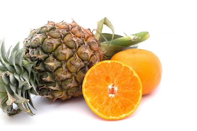 Arancia e ananas sono collocati su uno sfondo bianco