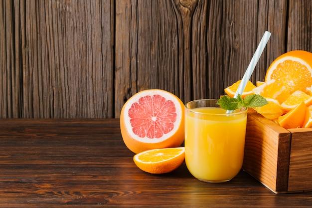 Arancia e succo di pompelmo su fondo in legno