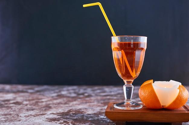 Arancia e un bicchiere di succo con tubo giallo sul piatto di legno sul marmo