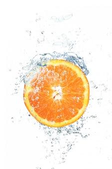 Arancia fresca che cade in acqua