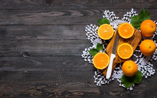 Arancia fresca con le foglie su fondo di legno. vista dall'alto,