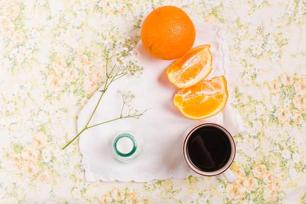 Arancia intera e fetta; tazza di caffè; gypsophila e bottiglia di latte su sfondo floreale