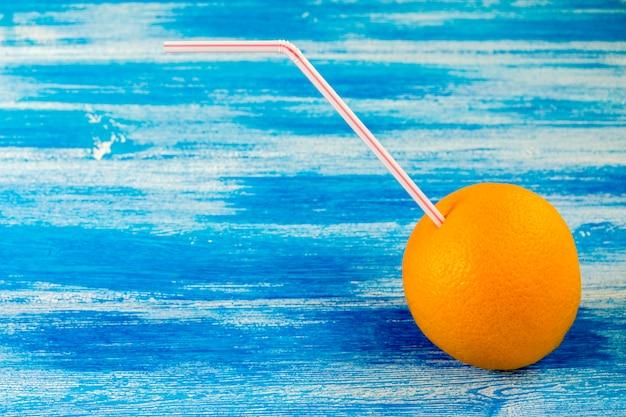 Arancia matura con tubo per cocktail sullo sfondo blu