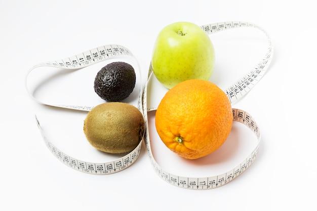 Arancia, mela, kiwi e avocado circondati da un metro a nastro