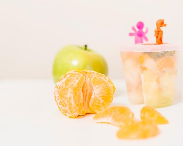 Arancia; muffa del ghiacciolo e mela sulla scrivania