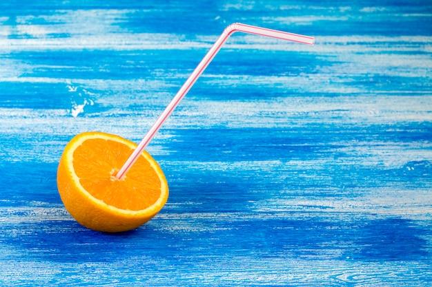 Arancio a fette con tubo per cocktail sullo sfondo blu