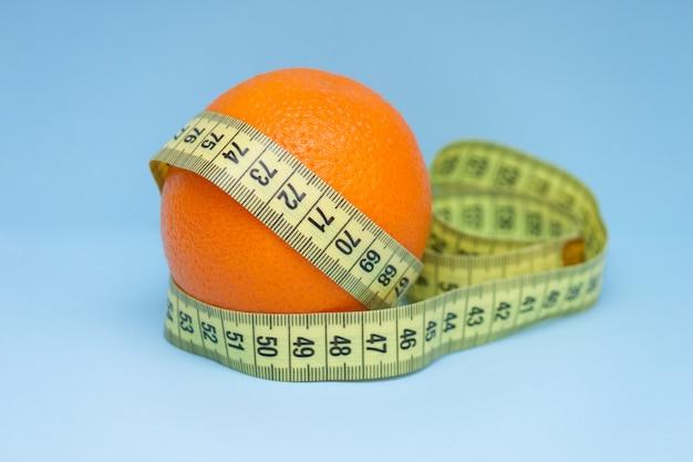 Arancio con nastro di misurazione avvolto attorno ad esso sullo sfondo blu.