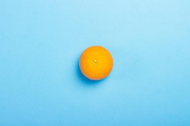 Arancione su una superficie blu. minimalismo. concetto di tropici, alimentazione sana, vitamine. vista piana, vista dall'alto.