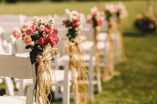 Archi di corda intrecciano mazzi di fiori rosa a sedie bianche