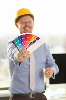 Architector in piedi con campioni di fasce di colore