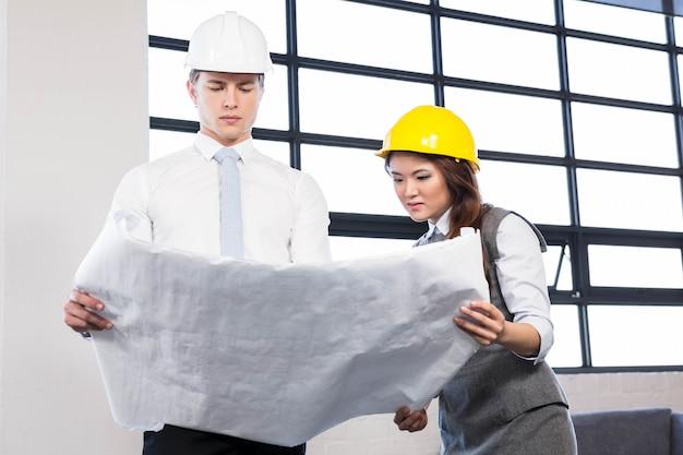Architetti che esaminano cianografia in ufficio
