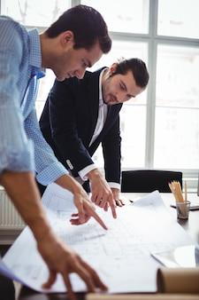 Architetto arredatore che discute modello con il collega maschio