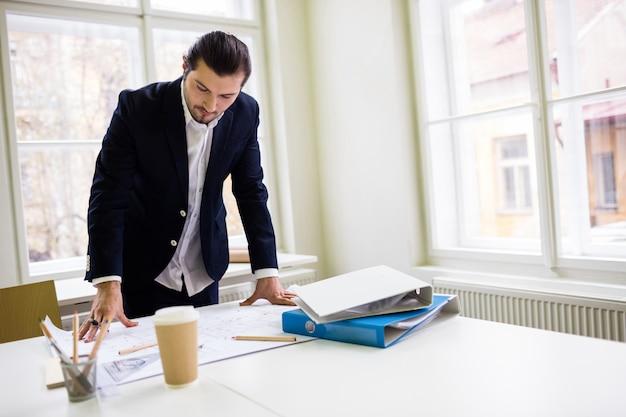 Architetto arredatore che esamina modello sul tavolo