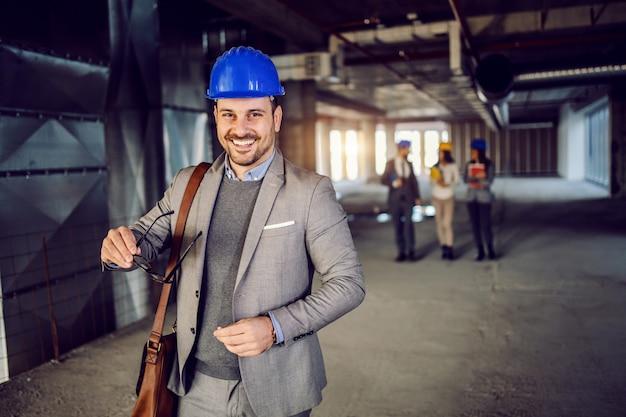 Architetto caucasico attraente sorridente con il casco sulla testa che sta nella costruzione nel processo di costruzione