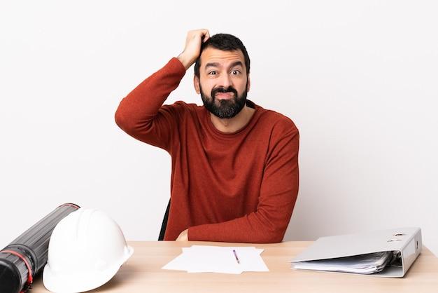 Architetto caucasico uomo con la barba in un tavolo con un'espressione di frustrazione e non comprensione