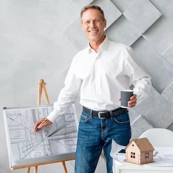 Architetto che guarda l'obbiettivo mentre mostra il suo piano