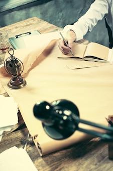 Architetto che lavora al tavolo da disegno in ufficio oa casa.