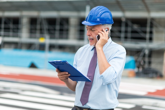 Architetto che parla al telefono davanti al cantiere