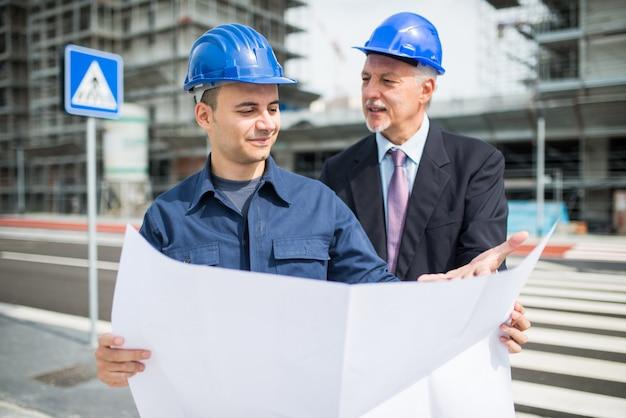 Architetto che parla con il responsabile del sito davanti a un cantiere