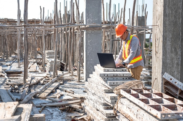 Architetto che per mezzo del computer portatile al cantiere