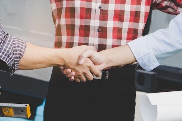Architetto che stringe le mani con il cliente nel cantiere.