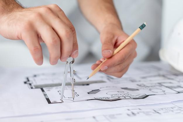 Architetto del primo piano che usando una bussola e una matita