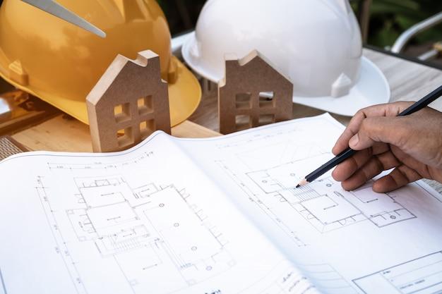 Architetto della camera che controlla piano domestico per costruzione sul documento del modello con la mini casa e cappello bianco