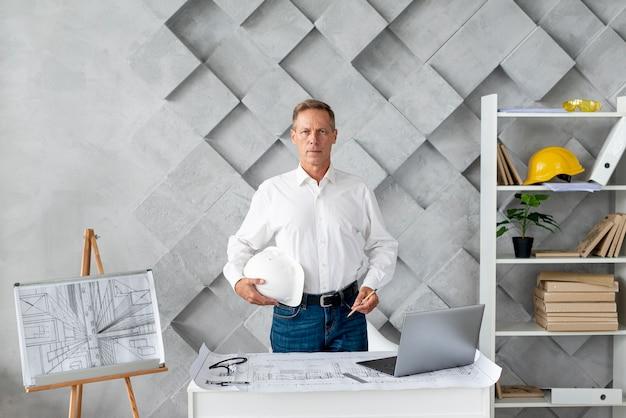 Architetto di colpo medio che posa nel suo ufficio