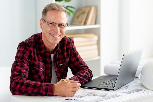Architetto di smiley con gli occhiali e guardando la telecamera