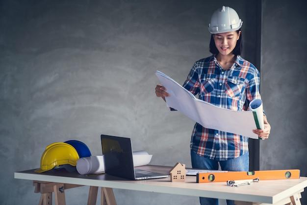 Architetto e ingegnere che lavorano un documento di disegno sulla pianificazione del progetto e sullo stato di avanzamento del programma di lavoro sul sito di costruzione di un edificio domestico