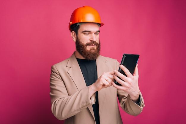 Architetto felice che lavora alla compressa sopra fondo rosa