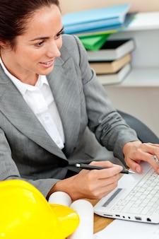 Architetto femminile concentrato che studia un progetto sul lavoro nel suo ufficio