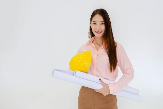 Architetto femminile in piedi con un cappello e lavorando