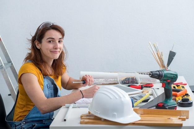 Architetto femminile sorridente dei giovani nell'ufficio