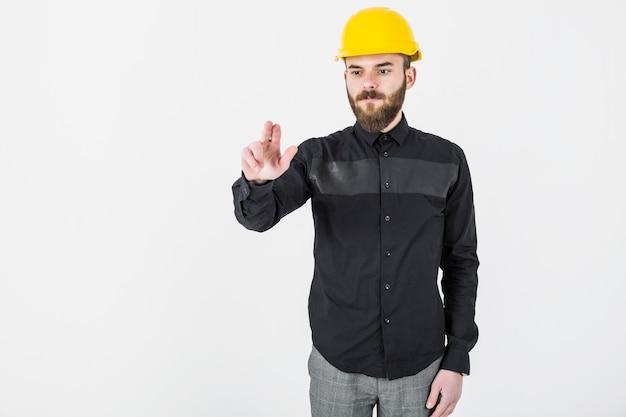 Architetto maschio che indossa gesturing giallo dell'elmetto protettivo