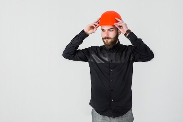 Architetto maschio sicuro che porta elmetto protettivo arancione luminoso