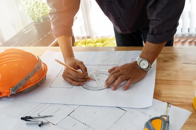 Architetto o ingegnere con matita e goniometro che lavora al progetto.