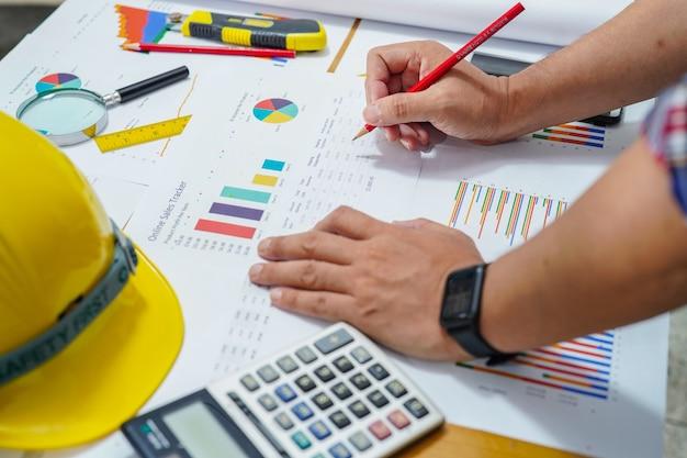 Architetto o ingegnere progetto di lavoro con grafico con strumenti in ufficio.