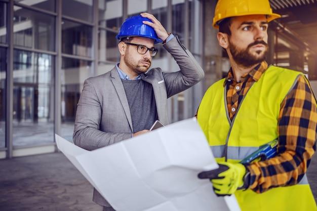 Architetto sconvolto che si tiene la testa e pensa all'errore che ha fatto sui progetti. operaio edile che tiene i modelli e distogliere lo sguardo.