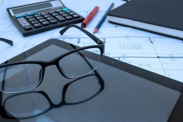 Architetto scrivania con piani di costruzione, tablet, occhiali presso studio architetto