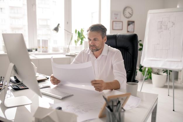 Architetto serio maturo in camicia bianca che controlla gli schizzi dal posto di lavoro durante la giornata lavorativa in ufficio