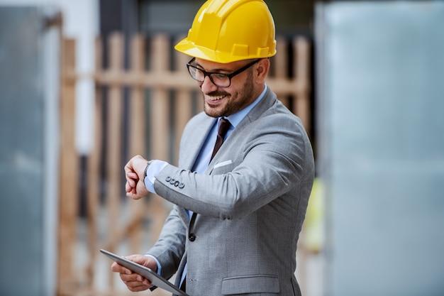 Architetto sorridente caucasico elegante attraente in vestito, con gli occhiali e casco sulla testa che sta al cantiere e che tiene compressa mentre guardando orologio.