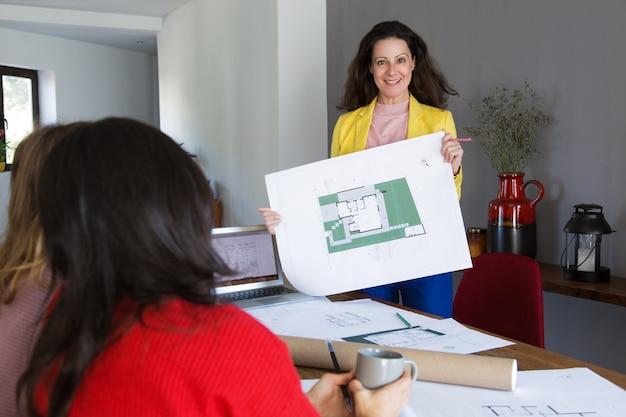 Architetto sorridente che mostra la progettazione della casa ai clienti o ai colleghi