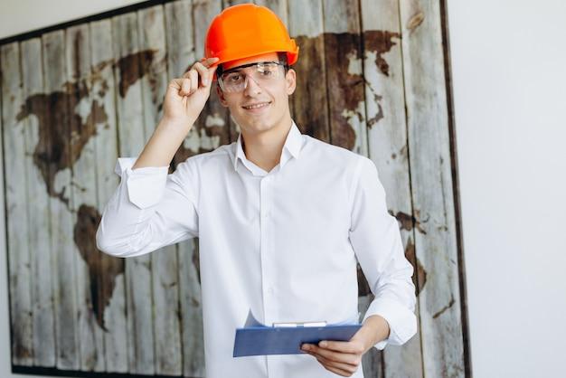 Architetto sorridente nel casco lavorando in ufficio