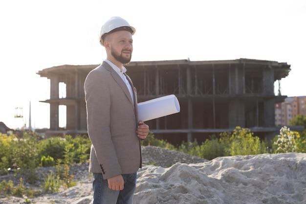 Architettura professionale in piedi al cantiere con cappello duro bianco e holding blueprint