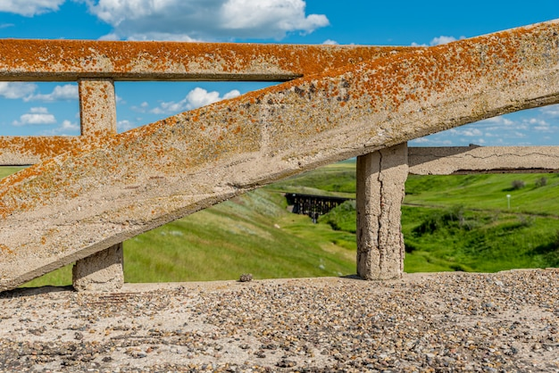 Arco coperto di licheni dal ponte di cemento di scotsguard, sk con un tressle ferroviario storico sullo sfondo