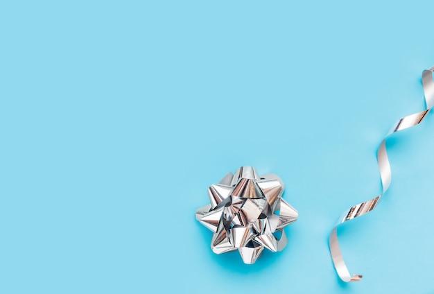 Arco d'argento della stagnola e nastro d'argento dell'imballaggio su fondo blu